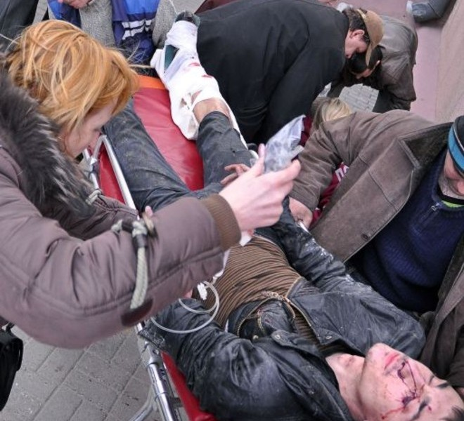 A woman helps a man injured in a bomb blast at a metro station in downtown Minsk, on April 11, 2011. At least 11 people were killed and a 100 wounded in the blast at a metro station near Belarus President Alexander Lukashenko's office in Minsk, Belarussian television said. AFP PHOTO / SERGEY BALAY