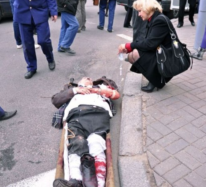 A woman helps a man injured in a blast at a metro station in downtown Minsk on April 11, 2011. At least seven people were killed in a blast at a metro station near Belarus President Alexander Lukashenko's office in Minsk, Belarussian television said. AFP PHOTO / SERGEY BALAY