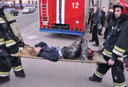 Firemen carry a woman injured in a bomb blast at a metro station in downtown Minsk, on April 11, 2011. At least 11 people were killed and a 100 wounded in the blast at a metro station near Belarus President Alexander Lukashenko's office in Minsk, Belarussian television said. AFP PHOTO / SERGEY BALAY
