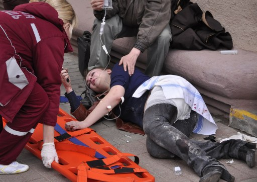 Emergency doctors help a woman injured in a bomb blast at a metro station in downtown Minsk, on April 11, 2011. At least 11 people were killed and a 100 wounded in the blast at a metro station near Belarus President Alexander Lukashenko's office in Minsk, Belarussian television said. AFP PHOTO / SERGEY BALAY
