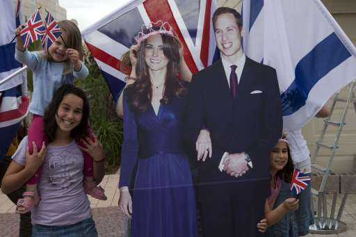 Israelis of British origin pose next to images of Prince William and Kate Middleton in their home balcony at the Israeli town of Modin as they decorate their house to celebrate tomorrow's royal wedding on April 28, 2011. Britain's Prince William is to marry his fiancee Kate Middleton at Westminster Abbey in London on April 29, 2011. AFP PHOTO /MENAHEM KAHANA