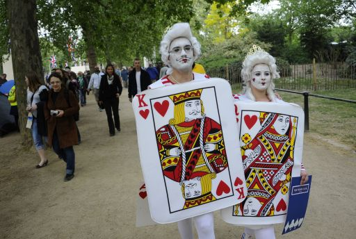 Royal fans dressed as King and Queen of Hearts walk along the Mall in central London, ahead of the royal wedding, on April 28, 2011. Britain's Prince William will marry his fiancee Kate Middleton at Westminster Abbey in London, on April 29, 2011. AFP PHOTO/ PIERRE-PHILIPPE MARCOU