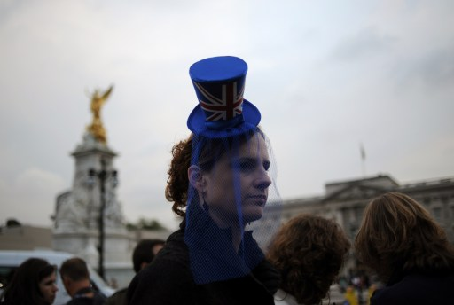 A woman wears a top hat with a Union Jack flag as she walks in front of Buckingham Palace in London on April 28, 2011 on the eve of the Royal wedding. Britain's Prince William is to marry his fiancee Kate Middleton at Westminster Abbey in London on April 29, 2011. AFP PHOTO/DIMITAR DILKOFF