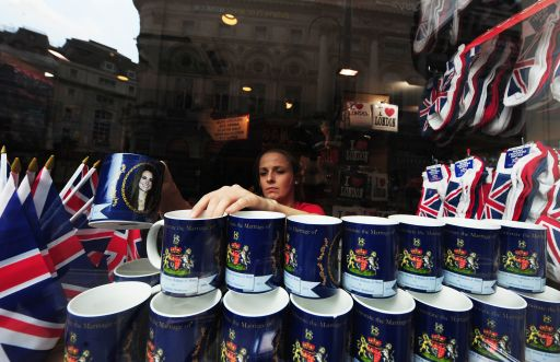 A woman arranges souvenir mugs in a shop in central London on April 28, 2011 on the eve of the Royal wedding. Britain's Prince William is to marry his fiancee Kate Middleton at Westminster Abbey in London on April 29, 2011. AFP PHOTO/JOE KLAMAR