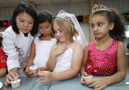 Students at the Alice Smith British school decorate cupcakes in honour of the British Royal wedding in Kuala Lumpur on April 29, 2011. British expatriates and others around the Asia-Pacific region are gearing up to watch the pomp and festivities of the British royal extravaganza in London on April 29 where Britain's Prince William will marry Kate Middleton at Westminster Abbey.  AFP PHOTO / KAMARUL AKHIR
