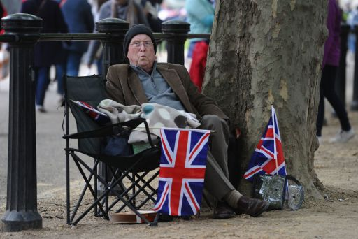 A royal supporter waits along the processional route on the day of the wedding of Britain's Prince William and Kate Middleton, in central London, on April 29, 2011. AFP PHOTO / PAUL ELLIS