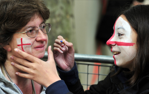 A royal supporter has her face painted as she waits along the processional route on the day of the wedding of Britain's Prince William and Kate Middleton, in central London, on April 29, 2011. AFP PHOTO / GLYN KIRK