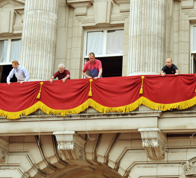 LONDON, ENGLAND - APRIL 29:  Staff dress the balcony at Buckingham Palace ahead of the Royal Wedding of Prince William to Catherine Middleton at Westminster Abbey on April 29, 2011 in London, England. The marriage of the second in line to the British throne is to be led by the Archbishop of Canterbury and will be attended by 1900 guests, including foreign Royal family members and heads of state. Thousands of well-wishers from around the world have also flocked to London to witness the spectacle and pageantry of the Royal Wedding. (Photo by John Stillwell - WPA Pool/Getty Images)