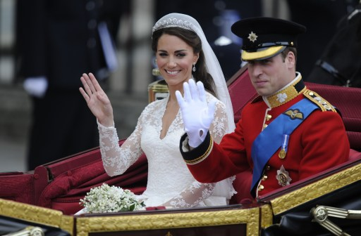 Britain's Prince William and his wife Kate, Duchess of Cambridge, wave as they travel in the 1902 State Landau carriage along the Processional Route to Buckingham Palace, in London, on April 29, 2011.  AFP PHOTO / ODD ANDERSEN