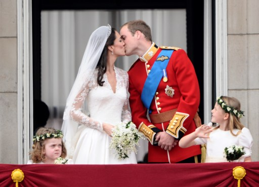Britain's Prince William kisses his wife Kate, Duchess of Cambridge, on the balcony of Buckingham Palace, after the wedding service, on April 29, 2011, in London.    AFP PHOTO / LEON NEAL