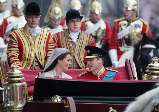 Britain's Prince William chats with his wife Kate, Duchess of Cambridge, as they travel in the 1902 State Landau carriage along the Processional Route to Buckingham Palace, in London on April 29, 2011.     AFP PHOTO/ POOL/ MATT CARDY