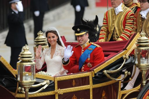 Britain's Prince William and his wife Kate, Duchess of Cambridge, wave as they travel in the 1902 State Landau carriage along the Processional Route to Buckingham Palace, in London, on April 29, 2011. AFP PHOTO / BEN STANSALL