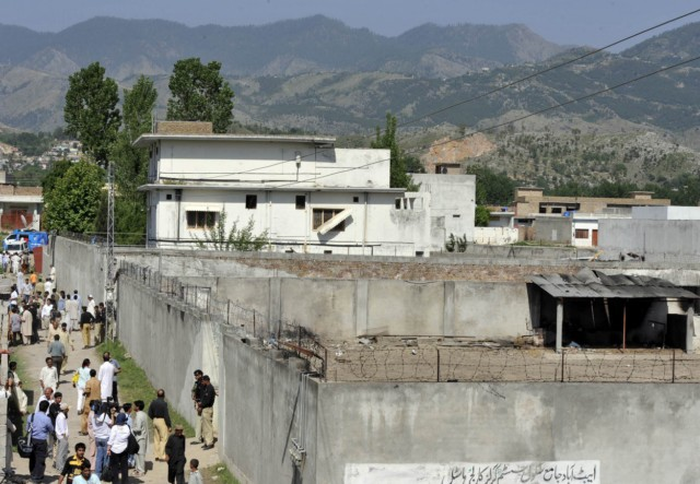 Pakistani police, media personel and local residents gather outside a burnt compound at the hideout of Al-Qaeda leader Osama bin Laden following his death by US Special Forces in a ground operation in Abbottabad on May 3, 2011. The United States warned it would probe how Osama bin Laden managed to live in undetected luxury in Pakistan, as gripping details emerged about the US commando raid that killed the Al-Qaeda kingpin. Officials said DNA tests had proven conclusively that the man shot dead by US special forces in Abbottabad was indeed the Islamist terror mastermind who boasted about the deaths of 3,000 people in the September 11 attacks of 2001. AFP PHOTO/ AAMIR QURESHI