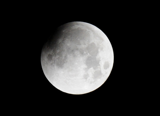 The moon is partially covered as a lunar eclipse gets underway, as seen from the Philippine Observatory in Manila before dawn on June 16, 2011Astronomers in parts of Europe, Africa, Central Asia and Australia were hoping for clear skies on Wednesday to enjoy a total lunar eclipse, the first of 2011 and the longest in nearly 11 years. A total lunar eclipse occurs when Earth casts its shadow over the Moon. The lunar face can sometimes turn reddish, coppery-brown or orange, tinged by light from the Sun that refracts as it passes through our atmosphere.         AFP PHOTO / JAY DIRECTO