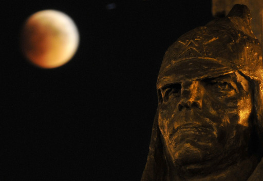 A portion of the moon crosses into the Earth's shadow seen above a head of the Red Army soldier's sculpture, a part of a monument to the Soviet founder Vladimir Lenin, in the southern Russian city of Stavropol, late on June 15, 2011. Astronomers in parts of Europe, Africa, Central Asia and Australia were hoping for clear skies on June 15 to enjoy a total lunar eclipse, the first of 2011 and the longest in nearly 11 years. AFP PHOTO / DANIL SEMYONOV