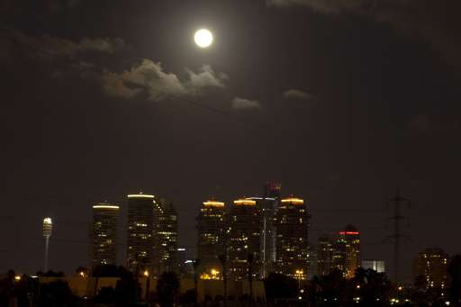 The moon rises over the Israeli coastal city of Tel Aviv before a total lunar eclipse on June 15, 2011. AFP PHOTO/JACK GUEZ
