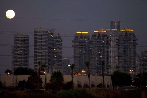A picture shows the moon rising over the Israeli coastal city of Tel Aviv before the start of a total lunar eclipse on June 15, 2011. AFP PHOTO/JACK GUEZ