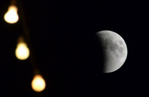 A picture shows the moon during a total lunar eclipse in Pakistan's central city of Multan on June 16, 2011. Astronomers in parts of Europe, Africa, Central Asia and Australia enjoy a total lunar eclipse today, the first of 2011 and the longest in nearly 11 years. A total lunar eclipse occurs when Earth casts its shadow over the Moon. The lunar face can sometimes turn reddish, coppery-brown or orange, tinged by light from the Sun that refracts as it passes through our atmosphere.  AFP PHOTO/ S.S. MIRZA
