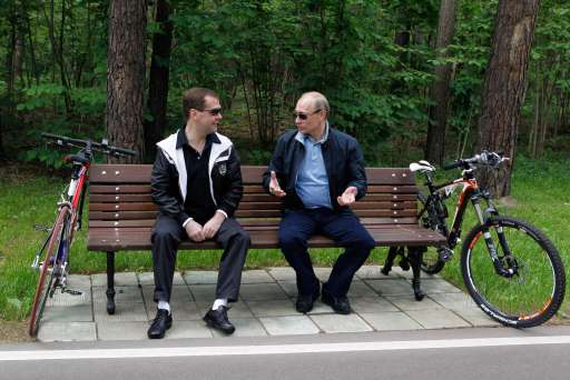 Russian President Dmitry Medvedev (L) speaks with Prime Minister Vladimir Putin (R) during a cycle  ride  in the residence of Gorky outside Moscow on June 11, 2011.  AFP PHOTO /RIA NOVOSTI / KREMLIN POOL / DMITRY ASTAKHOV