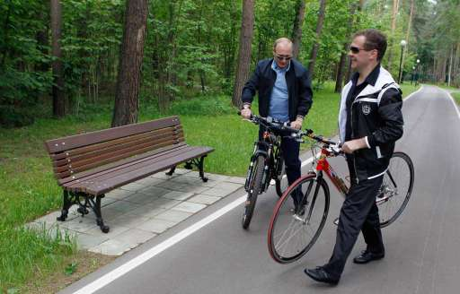 Russian President Dmitry Medvedev (R) and Prime Minister Vladimir Putin (L) carry their cycles during a walk  in the Gorky residence outside Moscow on June 11, 2011.  AFP PHOTO /RIA NOVOSTI / KREMLIN POOL / DMITRY ASTAKHOV