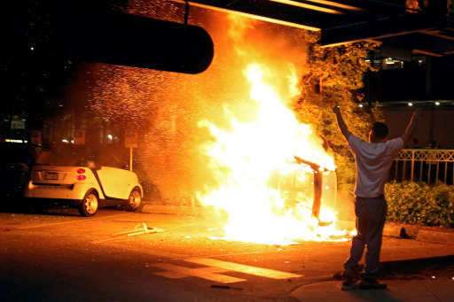 VANCOUVER, BC - JUNE 15: A person walks in front of a burning vehicle on June 15, 2011 in Vancouver, Canada. Vancouver broke out in riots after their hockey team the Vancouver Canucks lost in Game Seven of the Stanley Cup Finals.   Elsa/Getty Images/AFP== FOR NEWSPAPERS, INTERNET, TELCOS & TELEVISION USE ONLY ==