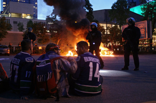 VANCOUVER, BC - JUNE 15: Riot police stand in front of two burning police cars as people look on June 15, 2011 in Vancouver, Canada. Vancouver broke out in riots after their hockey team the Vancouver Canucks lost in Game Seven of the Stanley Cup Finals.   Elsa/Getty Images/AFP== FOR NEWSPAPERS, INTERNET, TELCOS & TELEVISION USE ONLY ==