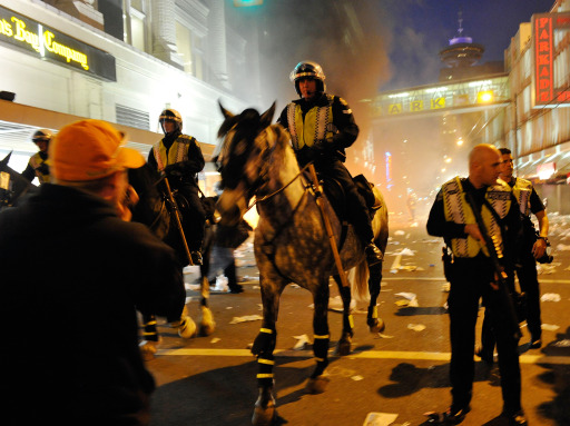 VANCOUVER, BC - JUNE 15: Police on horseback ride through the street past a fire on June 15, 2011 in Vancouver, Canada. Vancouver broke out in riots after their hockey team the Vancouver Canucks lost in Game Seven of the Stanley Cup Finals.   Rich Lam/Getty Images/AFP== FOR NEWSPAPERS, INTERNET, TELCOS & TELEVISION USE ONLY ==