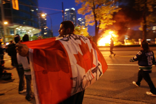 VANCOUVER, BC - JUNE 15: A person with a Candanian flag walks in front of a burning vehicle on June 15, 2011 in Vancouver, Canada. Vancouver broke out in riots after their hockey team the Vancouver Canucks lost in Game Seven of the Stanley Cup Finals.   Elsa/Getty Images/AFP== FOR NEWSPAPERS, INTERNET, TELCOS & TELEVISION USE ONLY ==