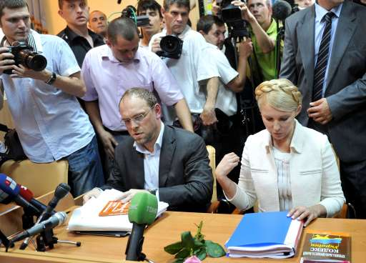 Ukraine's ex-prime minister Yulia Tymoshenko (R) makes the sign of the cross before the beginning her court hearing in Kiev on June 24, 2011. Ukraine's ex-prime minister Yulia Tymoshenko went on trial for alleged abuse of power, in a case she has dismissed as revenge by President Viktor Yanukovych.  AFP PHOTO/ SERGEI SUPINSKY