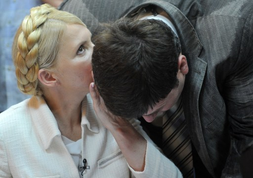 Ukraine's ex-prime minister Yulia Tymoshenko (L) speaks to her assistant at the beginning her court hearing in Kiev on June 24, 2011. Ukraine's ex-prime minister Yulia Tymoshenko went on trial for alleged abuse of power, in a case she has dismissed as revenge by President Viktor Yanukovych.  AFP PHOTO/ SERGEI SUPINSKY