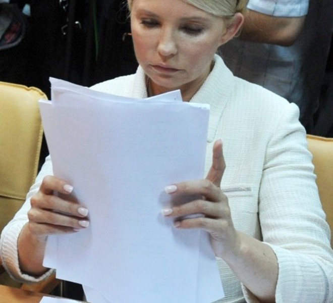 Ukraine's ex-prime minister Yulia Tymoshenko examines documents at the beginning of her court hearing in Kiev on June 24, 2011. Ukraine's ex-prime minister Yulia Tymoshenko went on trial for alleged abuse of power, in a case she has dismissed as revenge by President Viktor Yanukovych.  AFP PHOTO/ SERGEI SUPINSKY
