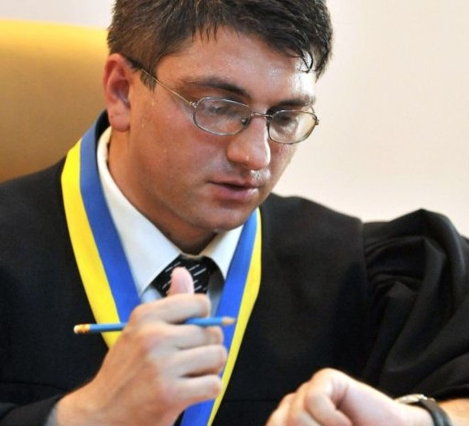 Judge Rodion Kyreyev checks his watch during the first day of the trial of Ukraine's ex-prime minister Yulia Tymoshenko in Kiev on June 24, 2011. Ukraine's ex-prime minister Yulia Tymoshenko went on trial for alleged abuse of power, in a case she has dismissed as revenge by President Viktor Yanukovych.  AFP PHOTO/ SERGEI SUPINSKY
