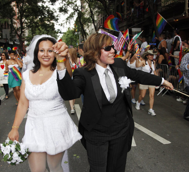 Paola Perez, left, and her partner Linda Collazo, march in the annual Gay Pride parade in Greenwich Village, Sunday, June 26, 2011 in New York.