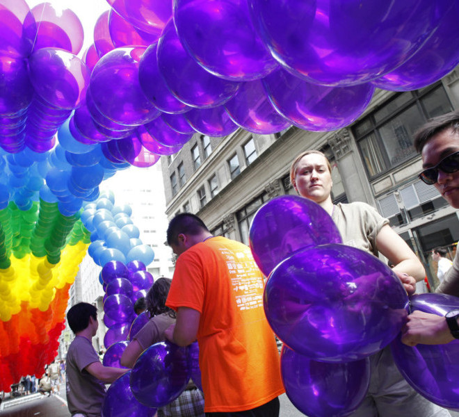 Kajsa Westman, second from right, of Stockholm, Sweden, and Victor Ng, right, of Seattle, tie balloons to a banner in preparation for the annual Gay Pride parade, Sunday, June 26, 2011 in New York. One of the world's oldest and largest gay pride parades was expected to become a victory celebration Sunday after New York's historic decision to legalize same-sex marriage.  The law signed by Gov. Andrew Cuomo on Friday doesn't take effect for 30 days.