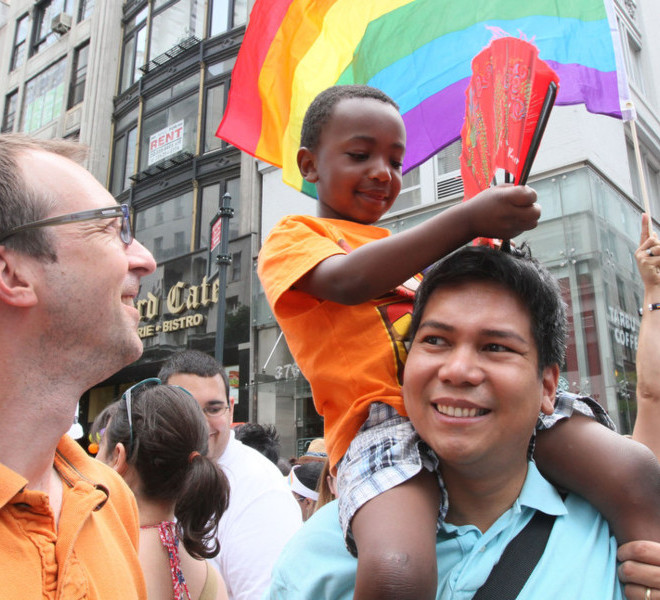 Christopher Goeken, left, his partner Glenn Magpantay, right, and their son Malcolm Magpantay, 4, from the Queens borough of New York, smile before the start of the Gay Pride Parade, Sunday, June 26, 2011, in New York.