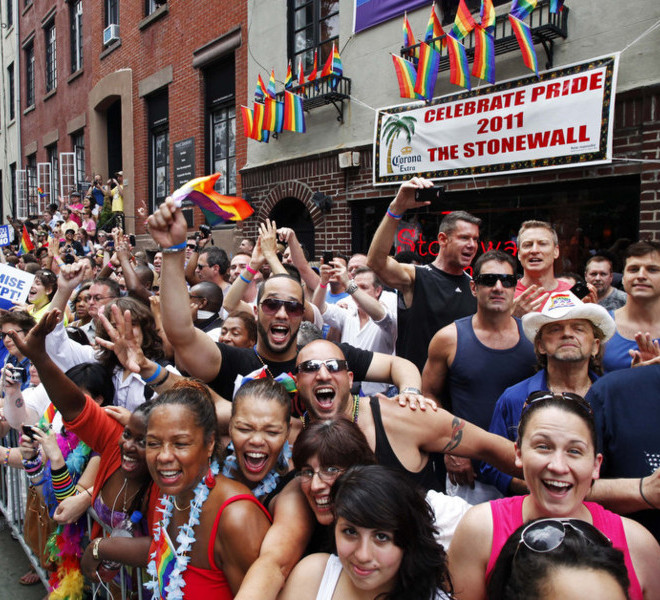 People cheer while standing in front of the Stonewall Inn on Christopher Street in Greenwich Village as the annual Gay Pride parade passes, Sunday, June 26, 2011 in New York.
