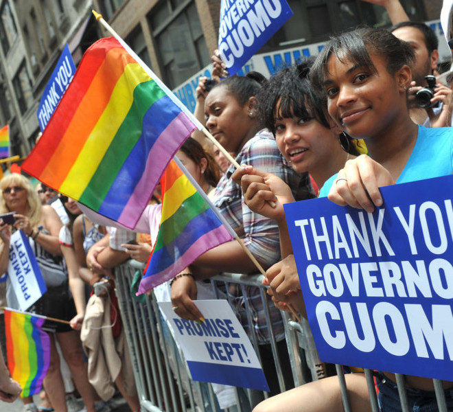 People hold signs thanking Governor Andrew Cuomo at the annual Heritage of Pride March, one of the world's oldest and largest gay pride parades, Sunday June 26, 2011, in New York.