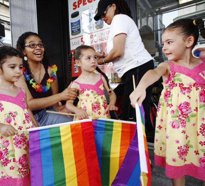 Jennifer Melendez, left, and her wife Juliza, standing, prepare for the annual Gay Pride parade with their daughters Natalia, left, Mahlani, center, and Alexis, Sunday, June 26, 2011 in New York.