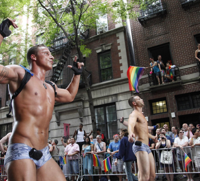Men flex their muscles while marching in the annual Gay Pride parade in Greenwich Village, Sunday, June 26, 2011 in New York.