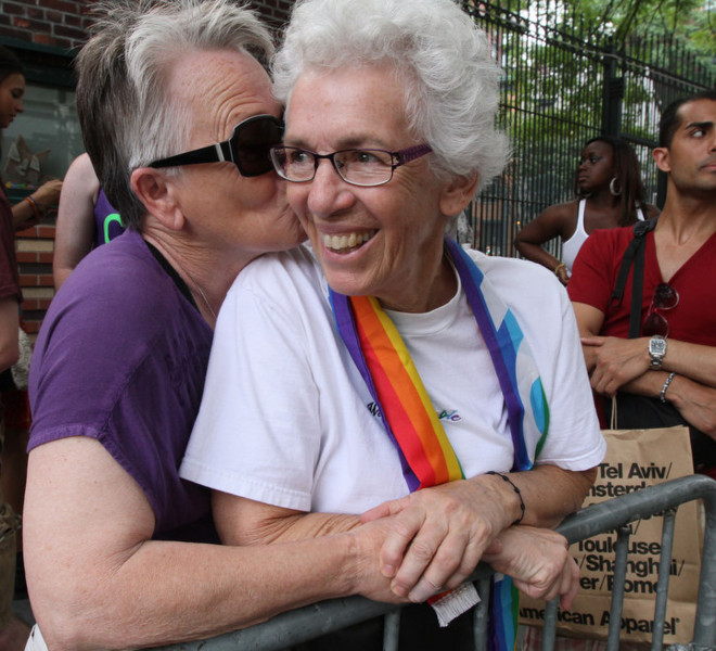 Shirley Gerow, 66, foreground left, kisses her partner Robin Burkhardt, 72, foreground right, from Central Valley, N.Y., as they watch the Gay Pride Parade Sunday June 26, 2011 in New York. Gerow and Burkhardt have been together for 16 years.
