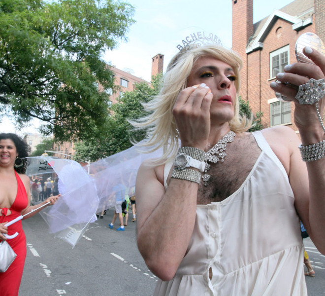 Matthew Garber, dressed as a bachelorette, foreground, touches up his make-up after marching in the Gay Pride Parade Sunday June 26, 2011 in New York.