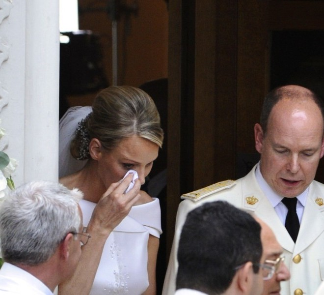 Princess Charlene of Monaco wipes a tear as she leaves with Prince Albert II of Monaco the Sainte Devote's Church where Princess Charlene left her bouquet after their religious wedding on July 2, 2011 in Monaco.      TOPSHOTS/AFP PHOTO/MIGUEL MEDINA