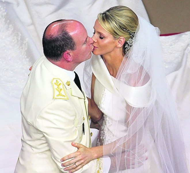 Prince Albert II of Monaco kisses Princess Charlene of Monaco during their religious wedding at the Main Courtyard of the Prince's Palace on July 2, 2011 in Monaco.    TOPSHOTS/AFP PHOTO/VALERY HACHE