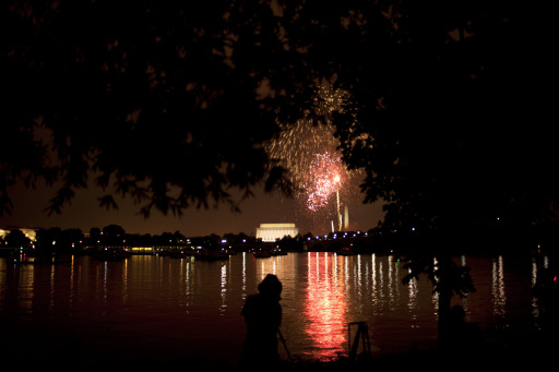 ARLINGTON, VA - JULY 04: A person watches as fireworks are shot over the National Mall in Washington, DC from along the shore of the Potomac River July 4, 2011 in Arlington, Virginia. The United States celebrated its 235th anniversary of declaring independence from the British Empire.   Brendan Smialowski/Getty Images/AFP== FOR NEWSPAPERS, INTERNET, TELCOS & TELEVISION USE ONLY ==