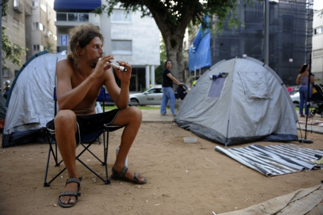 Israeli demonstrators walk at a tent camp in the centre of Tel Aviv on July 21, 2011 to protest against the rising prices of real estate in Israel. AFP PHOTO/MENAHEM KAHANA , A dog sits next to Israeli demonstrators sleeping at a tent camp in the centre of Tel Aviv on July 21, 2011 to protest against the rising prices of real estate in Israel. AFP PHOTO/MENAHEM KAHANA , Israeli demonstrators meditate at a tent camp in the centre of Tel Aviv on July 21, 2011 to protest against the rising prices of real estate in Israel. AFP PHOTO/MENAHEM KAHANA , An Israeli man walks past demonstrators sleeping at a tent camp in the centre of Tel Aviv on July 21, 2011 to protest against the rising prices of real estate in Israel. AFP PHOTO/MENAHEM KAHANA , Israeli demonstrators sleep at a tent camp in the centre of Tel Aviv on July 21, 2011 to protest against the rising prices of real estate in Israel. AFP PHOTO/MENAHEM KAHANA , Israeli flags flutter as demonstrators sleep at a tent camp in the centre of Tel Aviv on July 21, 2011 to protest against the rising prices of real estate in Israel. AFP PHOTO/MENAHEM KAHANA , An Israeli demonstrator uses an Israeli flag as a blanket while sleeping at a tent camp in the centre of Tel Aviv on July 21, 2011 to protest against the rising prices of real estate in Israel. AFP PHOTO/MENAHEM KAHANA , An Israeli rests on a bed set out amid dozens of tents pitched in the center of Tel Aviv on July 18, 2011, in protest against the rising prices of real estate in Israel. AFP PHOTO/MENAHEM KAHANA , A child looks at a flag as Israelis sit amid dozens of tents pitched in the center of Tel Aviv on July 18, 2011, in protest against the rising prices of real estate in Israel. AFP PHOTO/MENAHEM KAHANA , An Israeli protester uses his flag as a blanket as demonstrators sleep at a tent camp pitched in the centre of Tel Aviv on July 21, 2011 to protest against the rising prices of real estate in Israel. AFP PHOTO/MENAHEM KAHANA , Israelis sit amid dozens of tents pitched in the center of Tel Aviv on July 18, 2011, in protest against the rising prices of real estate in Israel. AFP PHOTO/MENAHEM KAHANA , Israelis sit outside dozens of tents pitched in the center of Tel Aviv on July 17, 2011 in protest against the rising prices of real estate in Israel. AFP PHOTO/DAVID BUIMOVITCH , Israelis sit amid dozens of tents pitched in the center of Tel Aviv on July 17, 2011 in protest against the rising prices of real estate in Israel. AFP PHOTO/DAVID BUIMOVITCH , An Israeli man plays a flute as he sits amid dozens of protest tents pitched in the center of Tel Aviv on July 17, 2011 against the rising prices of real estate in Israel. AFP PHOTO/DAVID BUIMOVITCH