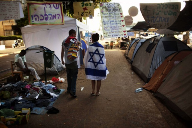 Israeli demonstrators walk at a tent camp in the centre of Tel Aviv on July 21, 2011 to protest against the rising prices of real estate in Israel. AFP PHOTO/MENAHEM KAHANA