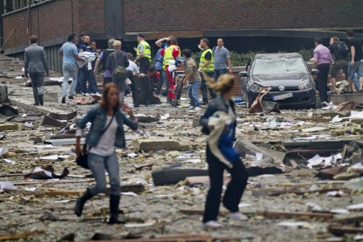Two women walk over debris while rescue workers in the background interact with people near an explosion site in Oslo after two bombs rocked the Norwegian capital on July 22, 2011. Militants staged twin bomb and shooting attacks in Norway Friday, leaving at least 11 dead as a blast tore through government buildings and a gunman opened fire at a youth meeting of the ruling party. Many were also reported wounded from the bomb blast in central Oslo and the shooting at a summer school meeting of Prime Minister Jens Stoltenberg's ruling Labour Party outside the capital. AFP PHOTO / SCANPIX / THOMAS WINJE OIJORD