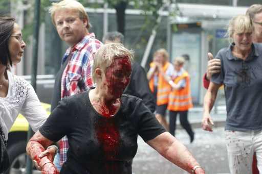 A woman covered in blood is taken by the arm after two bombs rocked the Norwegian capital of Oslo on July 22, 2011. Militants staged twin bomb and shooting attacks in Norway Friday, leaving at least 11 dead as a blast tore through government buildings and a gunman opened fire at a youth meeting of the ruling party. Many were also reported wounded from the bomb blast in central Oslo and the shooting at a summer school meeting of Prime Minister Jens Stoltenberg's ruling Labour Party outside the capital. AFP PHOTO / SCANPIX / ROALD BERIT
