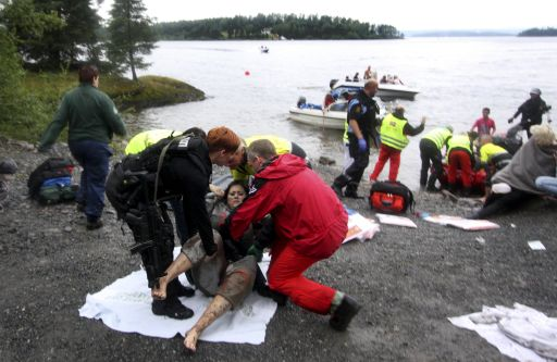 A wounded woman is brought ashore opposite Utaoya island (in the distance) after being rescued from a gunman who went on a killing rampage targeting participants in a Norwegian Labour Party youth organisation event on the island, some 40 km southwest of Oslo, on July 22 , 2011. At least 17 were killed in Friday's attacks in Norway, a bombing in central Oslo and a series of shootings on the island, and the figure could rise, a senior police officer said. Police had also found explosives on the island of Utoeya, where a gunman opened fire on young people at a summer camp organised by the ruling Labour Party, Sveinung Sponheim, acting commissioner for Oslo police, told reporters. AFP PHOTO / Svein Gustav Wilhelmsen  -- NORWAY OUT SWEDEN OUT DENMARK OUT --