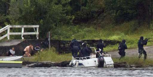 A swat team aim their weapons while people take cover during a shoot out at Utoeya island, some 40 km south west of the capital Oslo on July 22, 2011.  At least 17 were killed in Friday's attacks in Norway, a bombing in central Oslo and a series of shootings on an island just outside the capital, and the figure could rise, a senior police officer said. Police had also found explosives on the island of Utoeya, where a gunman opened fire on young people at a summer camp organised by the ruling Labour Party, Sveinung Sponheim, acting commissioner for Oslo police, told reporters. AFP PHOTO / Jan Bjerkeli  -- NORWAYOUT --